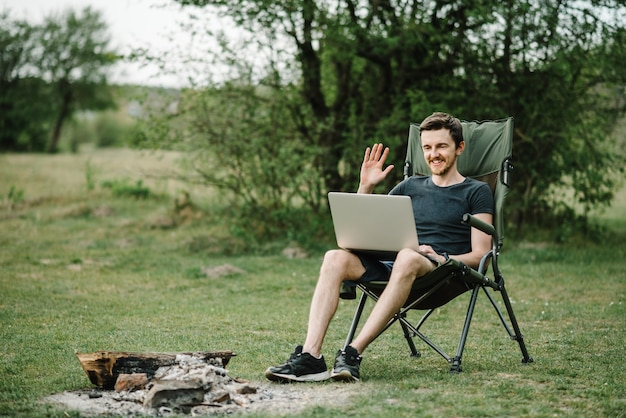 Comunicação com parentes, família online no laptop na natureza. homem instruindo a equipe na conferência ou consulta de trabalho remoto, trabalhador falar, falar em videochamada com colegas. Foto Premium