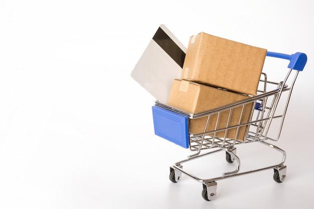 Conceito da compra: caixas ou caixas de papel e cartão de crédito no carrinho de compras azul no fundo branco. Foto Premium