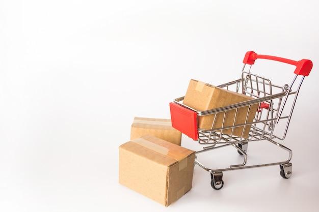 Conceito da compra: caixas ou caixas de papel no carrinho de compras vermelho no fundo branco. Foto Premium