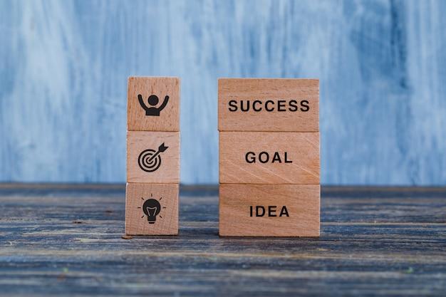 Conceito da estratégia empresarial com blocos de madeira na opinião lateral do fundo azul de madeira e sujo. Foto gratuita