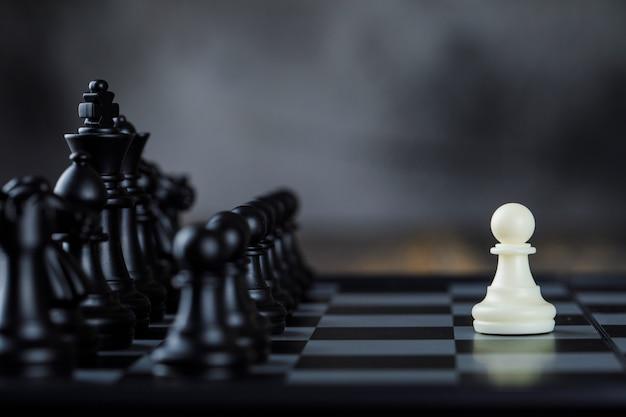 Conceito da estratégia empresarial com figuras no tabuleiro de xadrez na opinião lateral da tabela nevoenta e de madeira. Foto gratuita