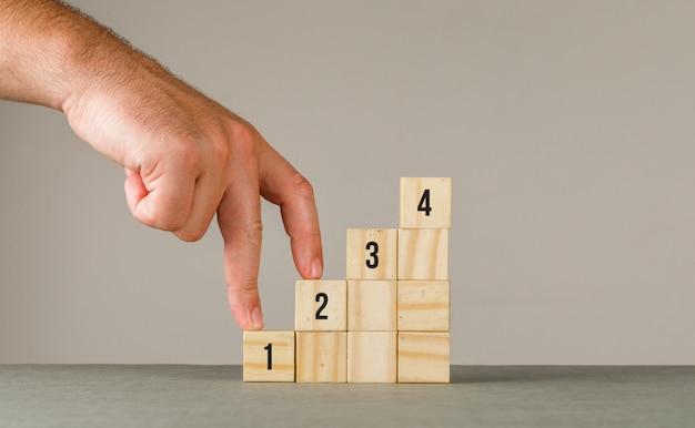 Conceito da estratégia empresarial na opinião lateral da parede cinzenta e branca. homem colocando os dedos na escada. Foto gratuita