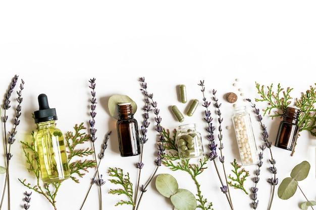 Conceito da medicina alternativa do eco da homeopatia - comprimidos clássicos da homeopatia, thuja, eucalipto, óleo essencial da alfazema e do aroma e ervas curas e na parede branca. flatlay. vista do topo. copyspace Foto Premium