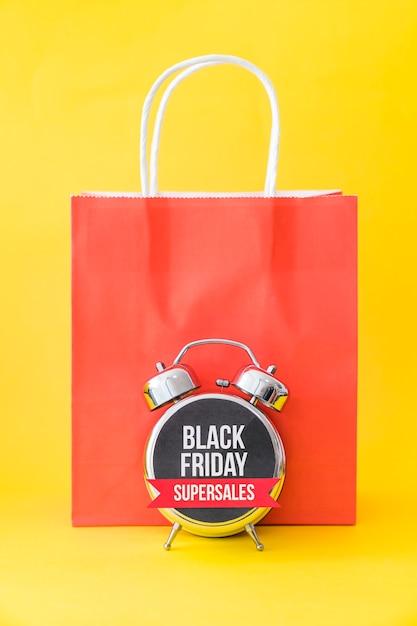 Conceito da sexta-feira negra com alarme na frente do saco vermelho Foto gratuita