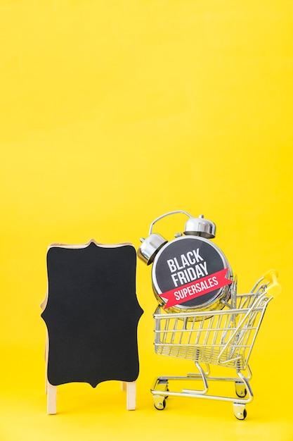 Conceito da sexta-feira negra com placa e despertador no carrinho Foto gratuita