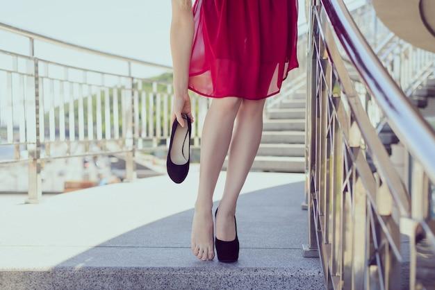 Conceito de acessórios de calçado de conforto freedom. close-up para ver a foto do clássico vestido de noite cor cereja bordô marrom coquetel, sapatos de mão, pernas perfeitas, sapatos de salto agulha, sapatos de formatura Foto Premium