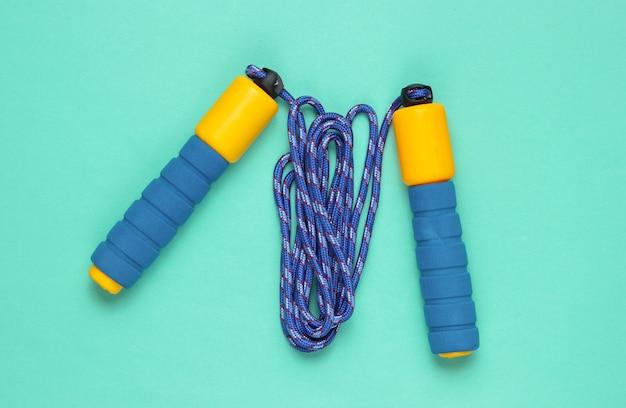 Conceito de adequação do minimalismo. pular corda em um fundo azul. Foto Premium