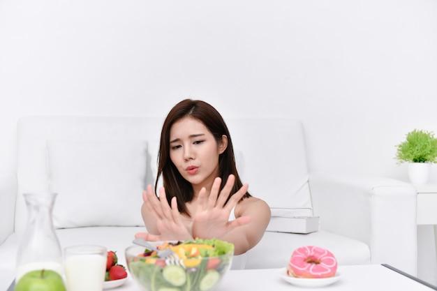 Conceito de alimentação saudável. lindas garotas estão escolhendo comer com as mãos Foto Premium