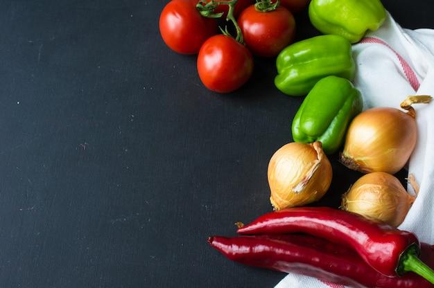 Conceito de alimentos orgânicos com variedade de legumes no quadro escuro Foto Premium