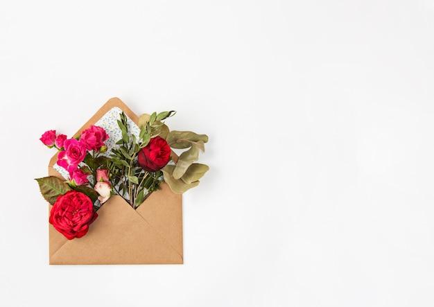 Conceito de amor ou dia dos namorados. lindas rosas vermelhas em envelopen Foto gratuita