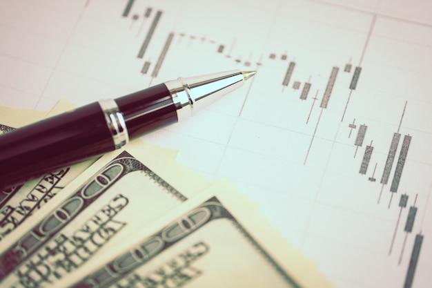 Conceito de análise de mercado de moeda. caneta em um gráfico conosco dólares. em tons. Foto Premium