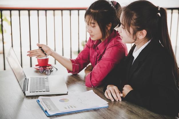 Conceito de análise de negócios. mulher de negócios que analisa originais de negócio, relatório finacial, trabalhando no laptop, telefone esperto móvel na mesa de escritório, fim acima. Foto gratuita