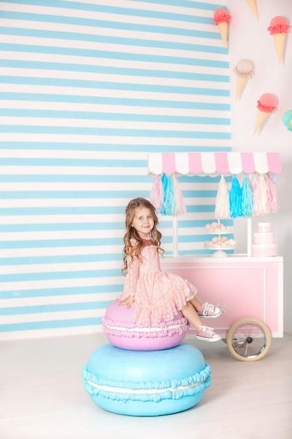 Conceito de aniversário e felicidade - feliz menina sentada em um bolo grande Foto Premium