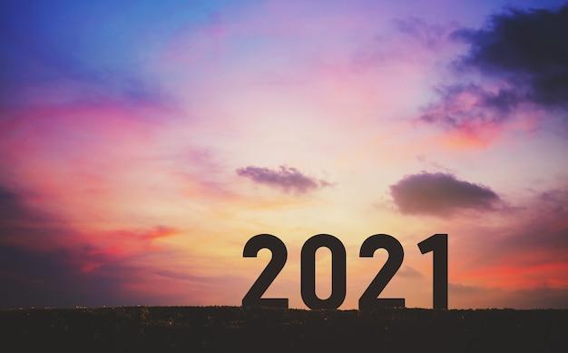 Conceito de ano novo 2021 com céu pôr do sol e fundo de montanha, estilo silhouette Foto Premium