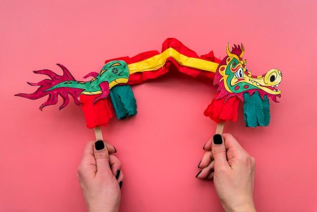 Conceito de ano novo chinês com mão feita dragão Foto gratuita