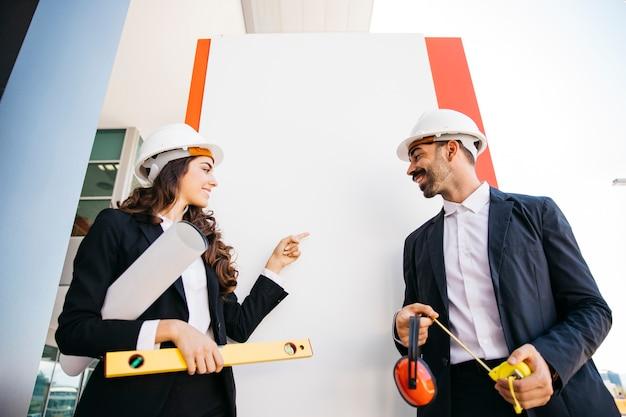 Conceito de apresentação com arquitetos que usam capacetes Foto gratuita