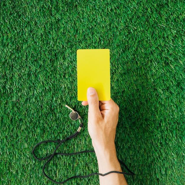 Conceito de árbitro com a mão segurando o cartão amarelo Foto Premium