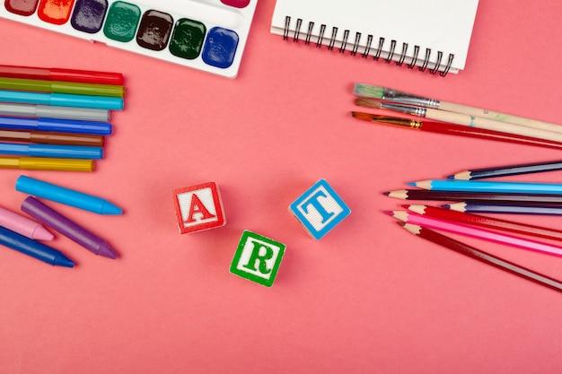 Conceito de arte. material escolar e cubos alfabéticos de madeira Foto Premium