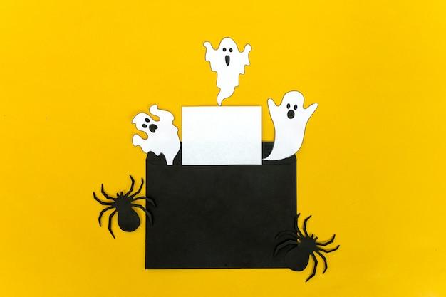 Conceito de artesanato halloween - morcego negro, gato, fantasma de papel em fundo amarelo Foto Premium