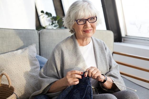 Conceito de artesanato, hobby, idade e aposentadoria. mulher idosa linda e elegante com rugas e cabelos curtos grisalhos aproveitando o tempo de lazer, sentada na sala de estar e tricotando um lenço estiloso para si mesma Foto gratuita