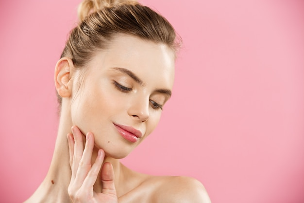 Conceito de beleza - close up retrato de garota caucasiano atraente com pele natural de beleza isolada no fundo rosa com espaço da cópia. Foto gratuita