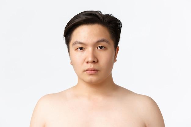 Conceito de beleza, cuidados com a pele e higiene. close de jovem asiático com pele propensa a acne, em pé nu sobre uma parede branca, anúncio de antes de usar produtos de limpeza para pele, parede branca Foto gratuita