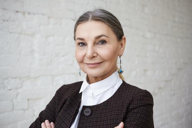 Conceito de beleza, estilo, moda e idade. feche o retrato de uma mulher elegante de 50 anos com cabelo grisalho e rosto enrugado posando contra uma parede de tijolos brancos Foto gratuita