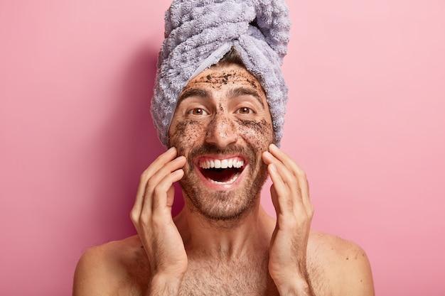 Conceito de beleza masculina. homem feliz e alegre aplica esfoliante de café no rosto, remove manchas escuras, quer parecer revigorado, enrolou uma toalha na cabeça Foto gratuita