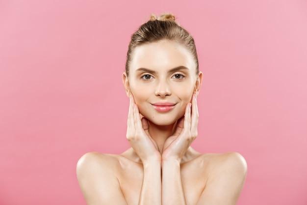 Conceito de beleza - mulher caucasiana bonita com pele limpa, maquiagem natural isolada no fundo rosa brilhante com espaço na cópia. Foto gratuita