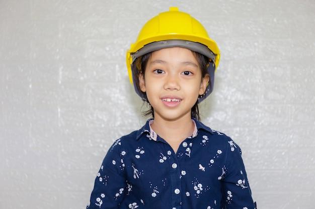 Conceito de carreira dos sonhos, retrato de garoto feliz engenheiro com capacete olhando para a câmera no fundo desfocado Foto Premium