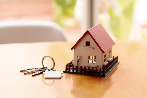 Conceito de casa modelo de brinquedo com chaves e fundo desfocado Foto Premium