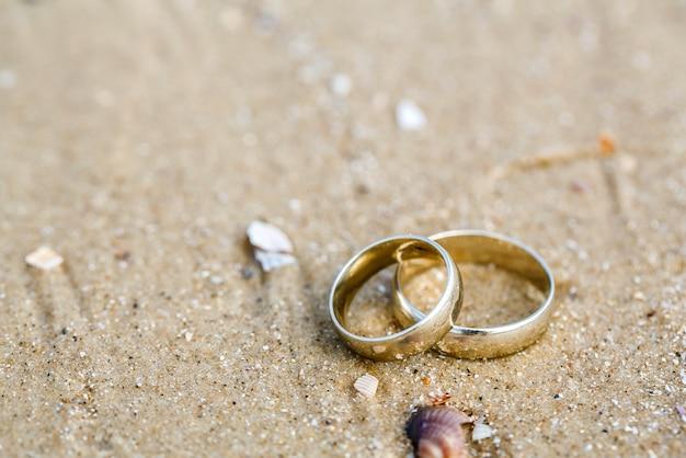 Conceito de casamento - anéis de casamento deitar na areia Foto Premium