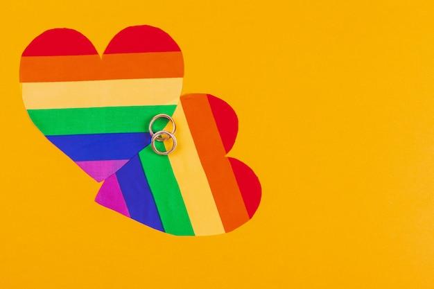 Conceito de casamento gay com bandeira do arco-íris e anéis | Foto Premium