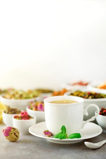 Conceito de chá com espaço de cópia. diferentes tipos de chá seco em tigelas de cerâmica branca e xícara de chá aromático Foto Premium