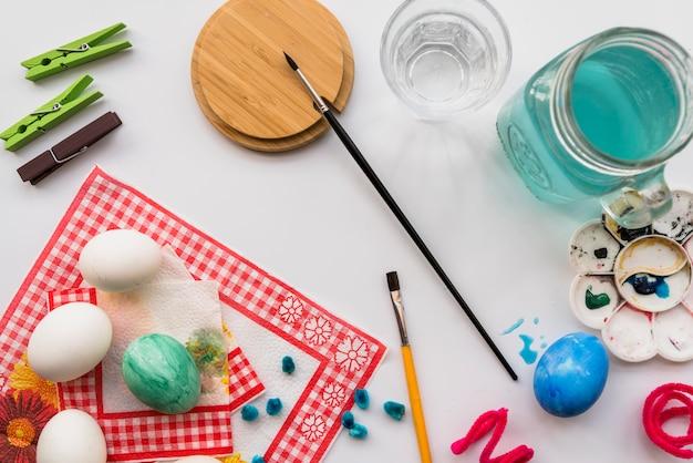 Conceito de colorir ovos perto de paleta e escovas Foto gratuita
