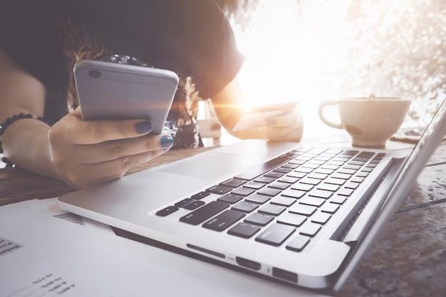 Conceito de comércio eletrônico. mulher que usa o portátil e o cartão de crédito para a compra em linha na cafetaria. Foto Premium
