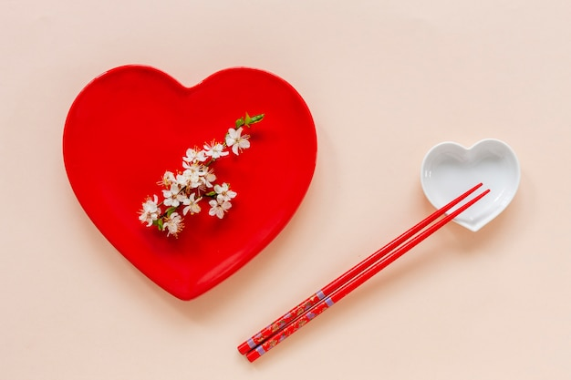 Conceito de comida japonesa floral primavera com galhos de árvores de cereja em flor e servindo com prato de forma de coração vermelho Foto Premium