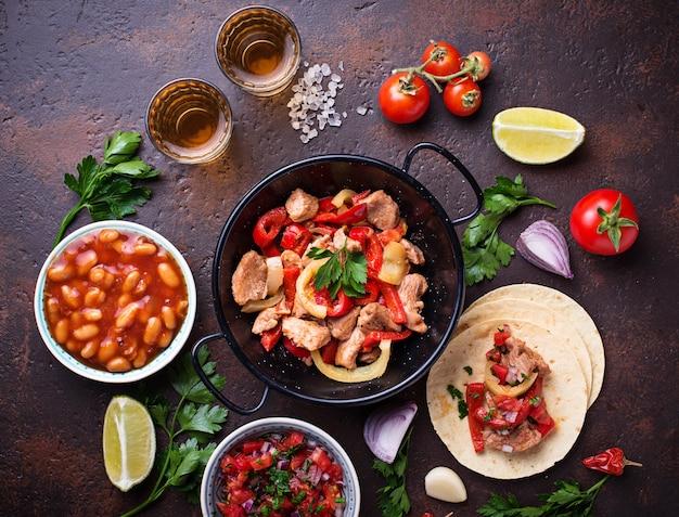 Conceito de comida mexicana. salsa, tortilla, feijão, fajitas e tequila Foto Premium