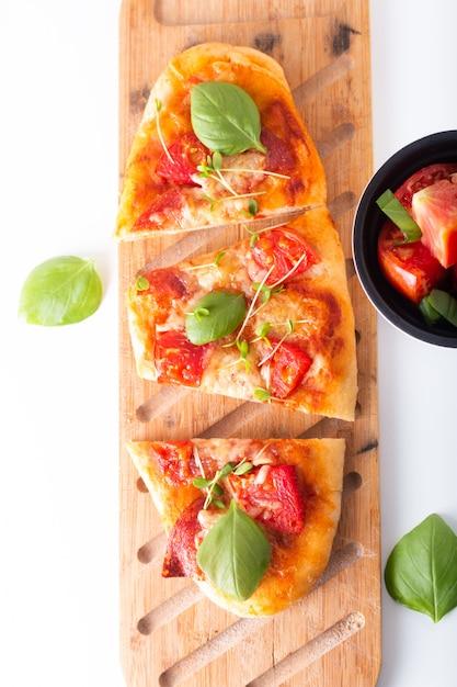 Conceito de comida pizza orgânica caseira com tomate, manjericão e presunto com espaço de cópia Foto Premium
