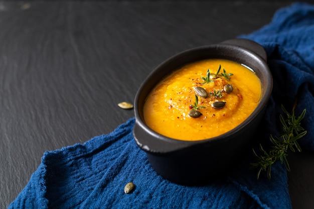 Conceito de comida saudável mistura quente sopa de legumes e sementes de abóbora em copo cerâmico preto Foto Premium