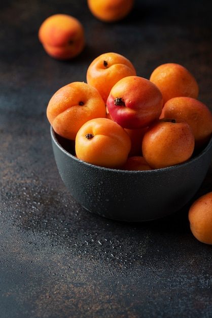Conceito de comida vegana saudável com damascos doces em uma superfície escura Foto Premium