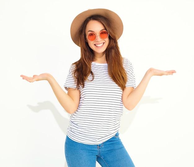 Conceito de comparação jovem morena com roupas casuais hipster e chapéu marrom exibindo algo em ambas as mãos planas Foto gratuita