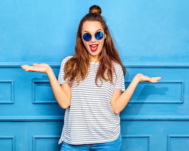 Conceito de comparação jovem morena em roupas de verão casual hipster exibindo algo em ambas as mãos planas para escolha semelhante do produto, posando perto da parede azul Foto gratuita