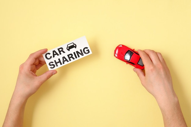 Conceito de compartilhamento de carro. mãos humanas segurando o texto e o modelo do carro de brinquedo vermelho assinam