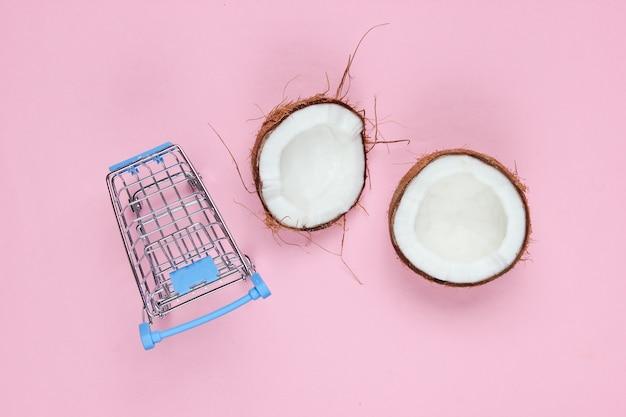 Conceito de compra de frutas. carrinho de compras, metades de coco quebrado em um fundo rosa. vista do topo Foto Premium