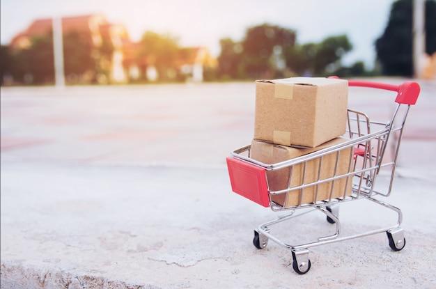 Conceito de compras: caixas ou caixas de papel no carrinho de compras no piso de concreto com espaço de cópia Foto Premium