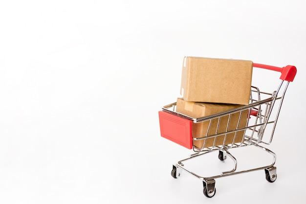Conceito de compras: caixas ou caixas de papel no carrinho vermelho em branco com espaço de cópia Foto Premium
