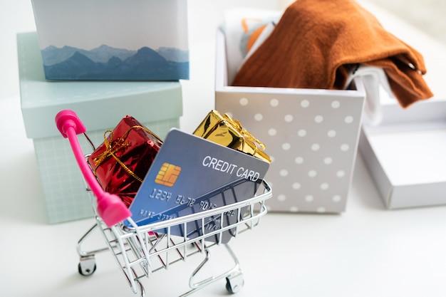 Conceito de compras on-line. carrinho de compras, caixas de encomendas, cartão de crédito, sobre a mesa em casa. copie o espaço, close-up Foto Premium