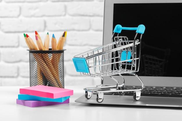 Conceito de compras on-line: mini carrinho de compras e laptop Foto Premium