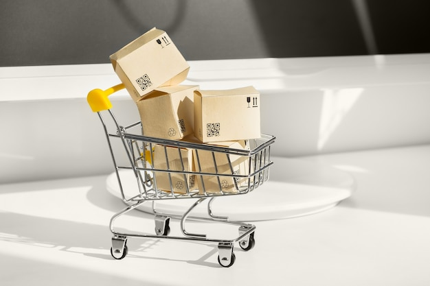 Conceito de compras online. carrinho de compras pequeno com muitas caixas de papel Foto Premium